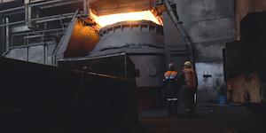 Employees In Front Of Metal Crucible Glowing Dark Factory Floor © Media Whalestock Dreamstime