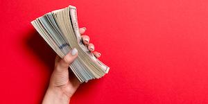 Hand Holding Money Bills Cash On Red Background © Mykola Sosiukin Dreamstime